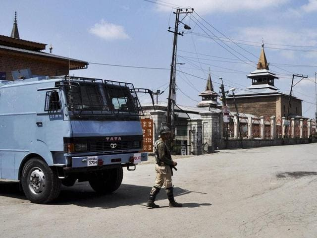 A security jawan stands guard on a deserted street in Srinagar.