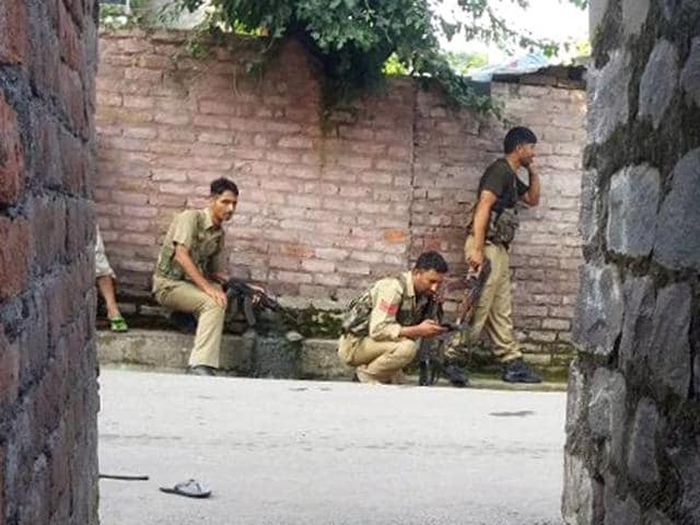 Police personnel take positions near a building where terrorists were hiding during an encounter on the outskirts of Poonch, in Jammu, on September 11, 2016.