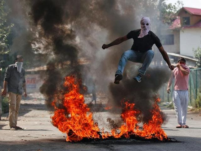 A man in a balaclava jumps over burning debris during a protest in Kashmir on Monday.