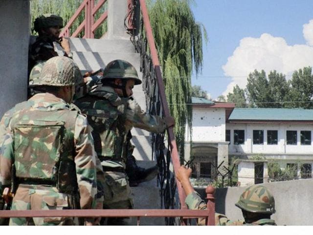 Security personnel take positions near the building where terrorists are hiding at Allah Pir area in Poonch district.