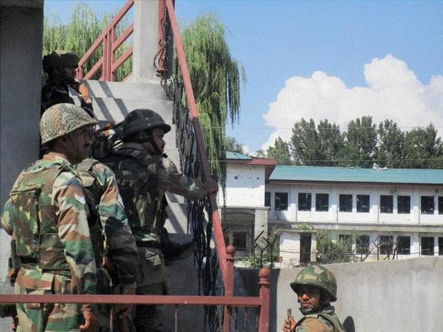 Security personnel take positions near the building where militants were hiding during the second day of encounter at Allah Pir area in Poonch on Monday.