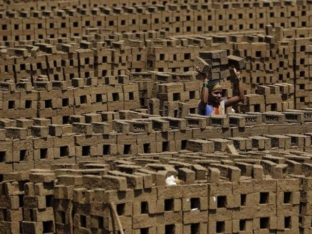 A labourer carries bricks at a kiln in Karjat.