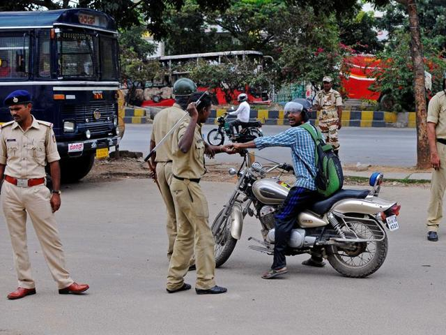 Police stop a man during a curfew over Cauvery water dispute, in Bengaluru.