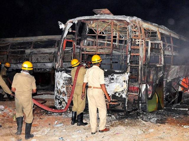 Firefighters trying to douse a fire in Tamil Nadu-bound buses after they were torched by pro-Kannada activists during a protest over Cauvery water row.(PTI Photo)