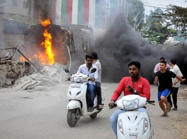 Men make their way past a burning lorry in Bengaluru, which was set on fire by protesters after the Supreme Court ordered Karnataka to release 12,000 cubic feet of water per second every day from the Cauvery river to neighbouring Tamil Nadu.
