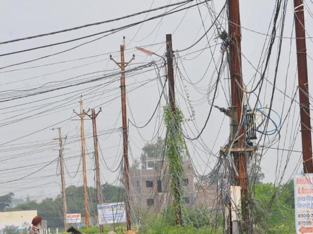 Electric wires hang over Kelodhal village road, located 10 kilometres away from Indore on Sunday.