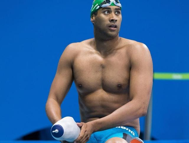 South African swimmer Achmat Hassiem puts on his prosthetic leg after competing in heat 1 of the men's 100-meter freestyle - S10 at the Olympic Aquatics Stadium, during the Paralympic Games.