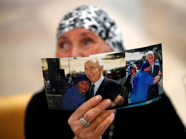 A woman shows her support as she holds up a photograph of herself with former Israeli President Shimon Peres.