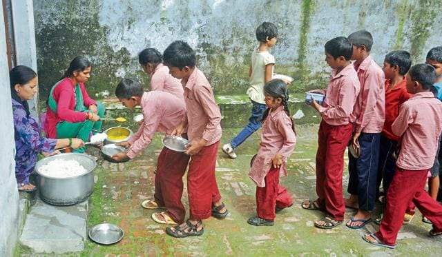 Students line up for their midday meal at a government school in Dehradun on Wednesday.