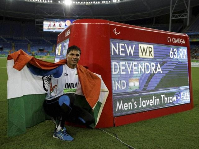 Devendra Jhajharia poses for pictures next to the scoreboard that shows his world record in the men's javelin throw F-46 event.