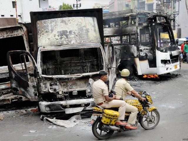 Two policemen ride past charred remains of vehicles in Bengaluru.