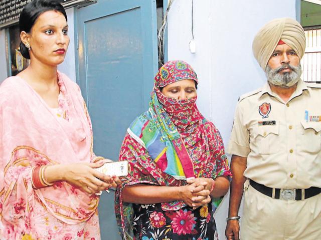 Prime accused Manjit Kaur (centre) in police custody at Ramdass police station in Ajnala on Wednesday.
