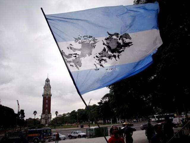 A man waves an Argentine flag with an image of the Falkland Islands in front of the Tower of the English during the commemoration of the 34th anniversary of the 1982 war between Britain and Argentina.