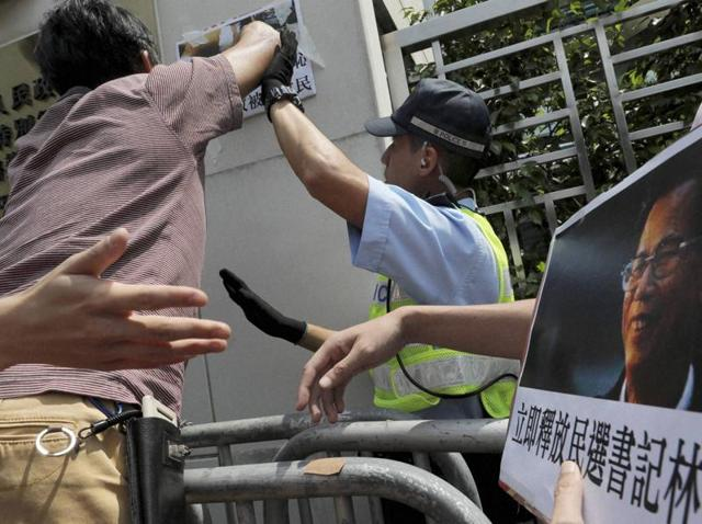 Hong Kong: A police officer tries to block protesters from pasting a picture of Wukan village's leader Lin Zuluan on the wall during a demonstration outside the Chinese central government's liaison office in Hong Kong on Wednesday. Police fired rubber bullets at villagers and arrested 13 people on Tuesday in an overnight crackdown to suppress demonstrations in  the fishing village that became internationally known five years ago for protesting land seizures.