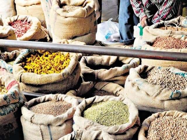In this photograph taken on September 20, 2011 workers and customers look through the goods at a wholesale food grain and commodities shop in the Agricultural Product Marketing Committee (APMC) Yard in Bangalore.