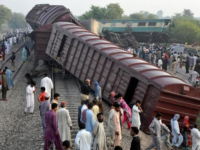 Locals mill around the scene where two trains collided near Multan in Pakistan on Thursday.