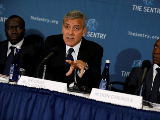 George Clooney (C), with fellow actor Don Cheadle (R) and The Sentry investigative journalist Brian Adeba (L), discusses The Sentry's investigation into the ongoing humanitarian crisis in South Sudan during a news conference at the National Press Club in Washington.