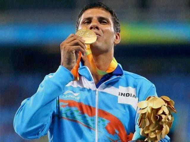 India's Devendra Jhajharia poses for the pictures next to the scoreboard that shows his world record.