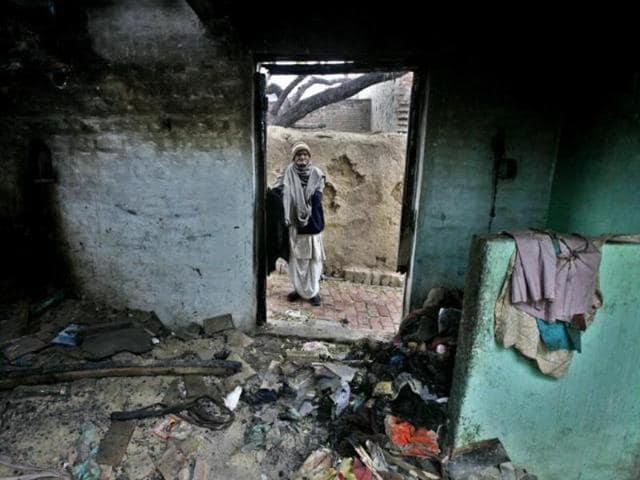 A man looks at a burnt and looted house in a village in Muzaffarnagar. In September 2013, three people were killed in Kawal village in Muzzaffarnagar in a riot following an incident of eve-teasing.(Raj K Raj/HT file)