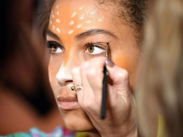 Models get ready backstage for Desigual during the New York Fashion Week. The Snapchat-inspired makeup made the show trend.