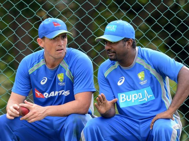 Australia's bowling consultant Muttiah Muralitharan (R) speaks with Australian cricketer Stephen O'Keefe.