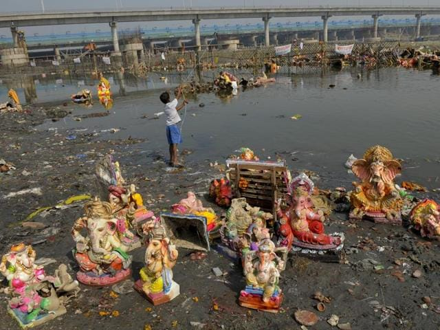 Scores of idols, lamps, flower garlands and other religious paraphernalia are salvaged from the river to be sold as scrap. (Burhaan Kinu/HT PHOTO)