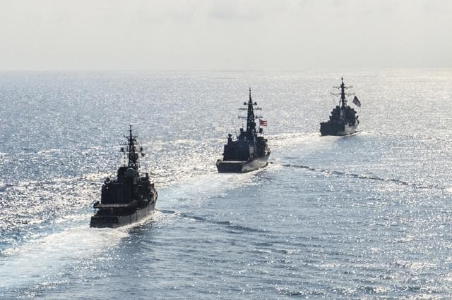 Arrleigh Burke-class guided-missile destroyer USS Mustin (DDG 89) transits in formation with Japan Maritime Self-Defense Force ships JS Kirisame (DD 104) and JS Asayuki (DD 132) during bilateral training in South China Sea on April 21, 2015.