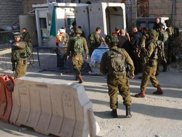 Israeli security forces gather at the scene of a reported Palestinian stabbing attack on an Israeli soldier near a Jewish settler enclave in the West Bank town of Hebron on Friday. Three alleged assailants were killed while carrying out attacks on Israelis, security forces said, shattering weeks of relative calm.