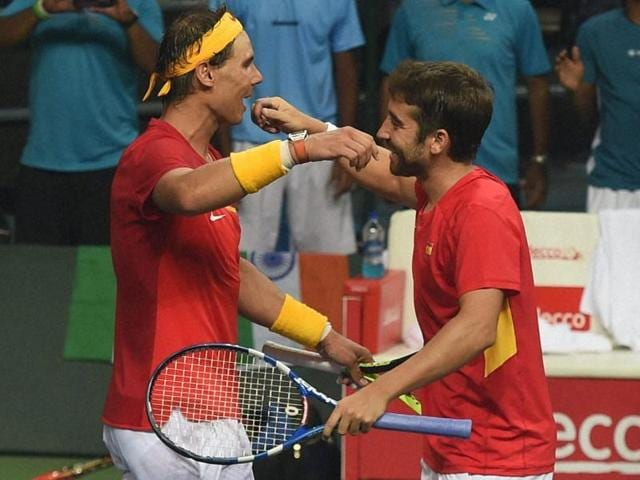 Rafael Nadal and Marc Lopez shake hands with Leander Paes and Saketh Myneni after the match.