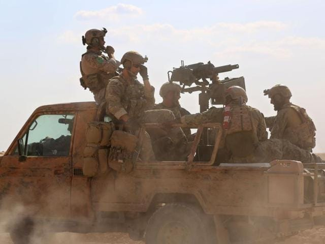 This file photo shows armed men in uniform identified by Syrian Democratic forces as US special operations forces riding in the back of a pickup truck in the village of Fatisah in the northern Syrian province of Raqqa.