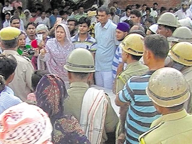 Villagers talk to policemen in Alwar's Rewada Ki Dhani  village where Hindu right-wing groups allegedly vandalised several Muslim houses.
