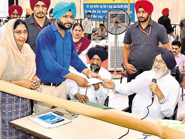 Punjab chief minister Parkash Singh Badal distributing cheques for development works during a 'sangat darshan' at Amargarh in Sangrur district on Saturday.