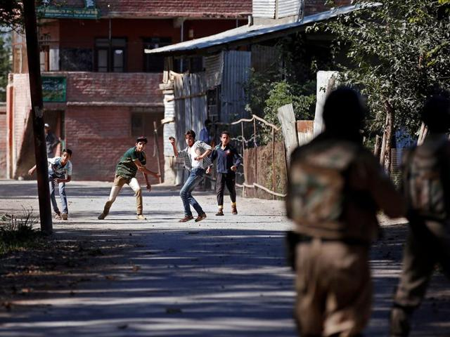 Youths hurl stones towards the police during a protest in Srinagar.