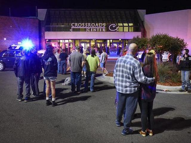 People stand near the entrance of Crossroads Center mall as officials investigate a reported multiple stabbing incident, in St Cloud, Minn.