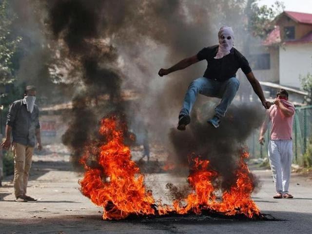 A man in a balaclava jumps over burning debris during a protest in Kashmir, Srinagar.