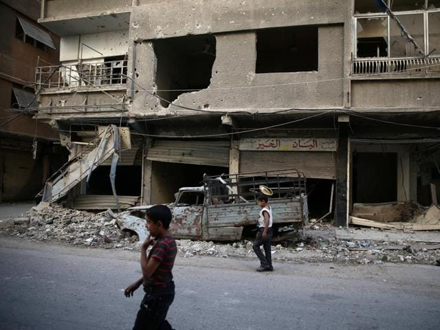 Children walk near damaged buildings in rebel-held Ain Tarma, eastern Damascus suburb of Ghouta, Syria.