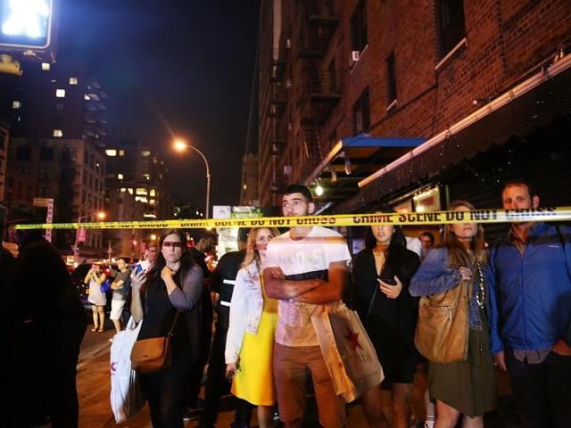 People stand behind police lines as firefighters, emergency workers and police gather at the scene of an explosion in Manhattan, New York City.