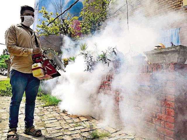 A worker fogging at the police lines quarters in Amritsar.