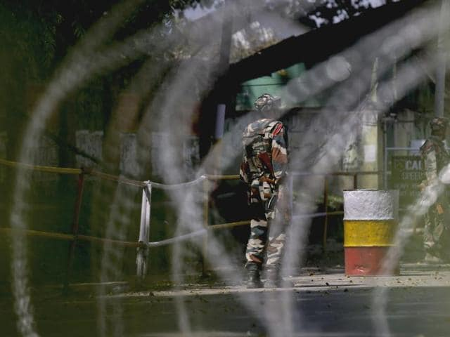 Soldiers guard the army base which was attacked by suspected rebels in the town of Uri, Jammu and Kashmir.