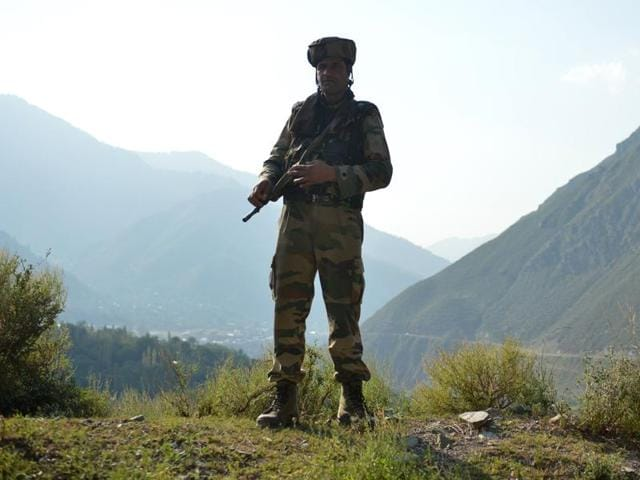 A soldier stands guard near the site of a gunbattle between soldiers and militants inside an army brigade headquarters near the border with Pakistan.