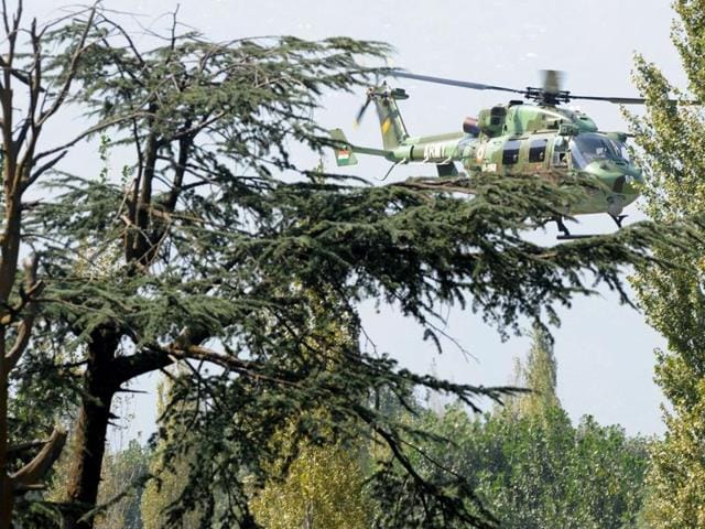 An Indian Army helicopter flies over the site of a gunbattle between soldiers and militants inside an army brigade headquarters near the border with Pakistan, known as the Line of Control (LoC), in Uri.