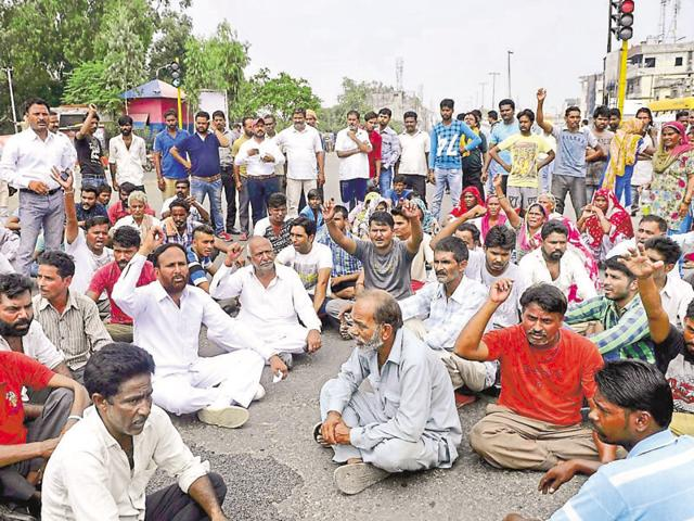 The family and municipal sanitation workers during a protest on Jagraon Bridge in Ludhiana on Saturday.