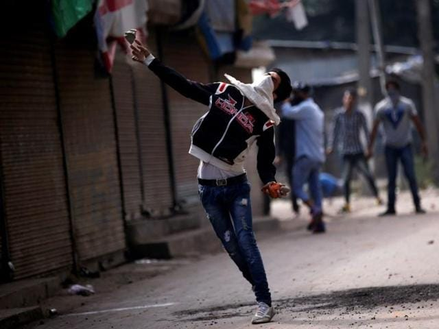 A protester throws a stone towards police during a protest against the recent deaths in Kashmir.