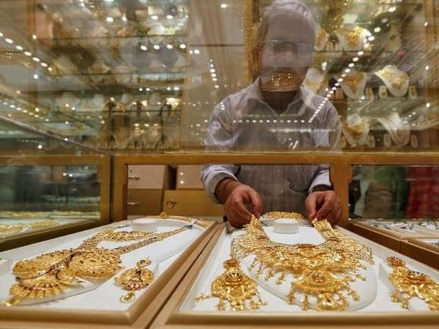 A salesman arranges a gold necklace in a display case inside a jewellery showroom in Kolkata.