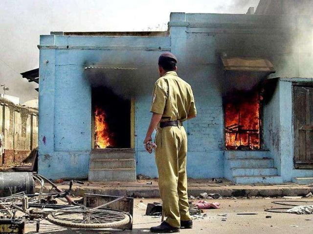 In this photograph taken on February 28, 2002, a policeman looks as fire rages in shops at the entrance to a mosque in Ahmedabad, following an attack by a mob.