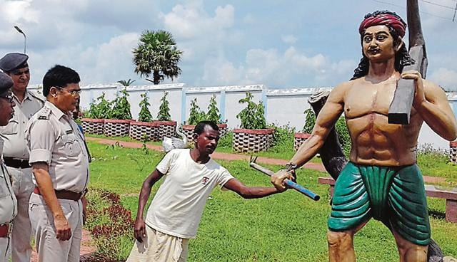 A villager shows one of the damaged statues to police officers at Bhognadih village in Sahibganj district on Sunday.