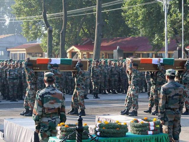 Indian army soldiers pay last respects to soldiers who died in the attack in Uri, at a ceremony in Srinagar.