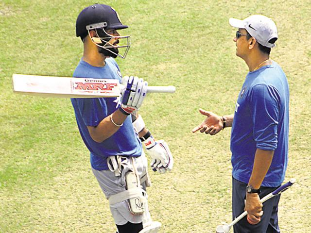 Captain Virat Kohli chats with batting coach Sanjay Bangar during a training session in Kanpur on Monday.