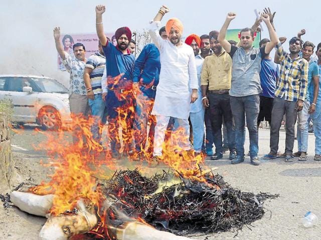 Congress workers burning an effigy of Pakistan during a protest at Bhandari Bridge in Amritsar on Monday.