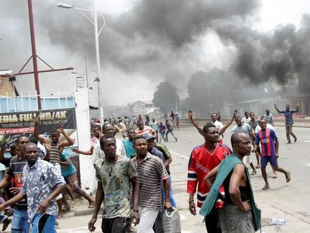 People stand near burning debris during election protests in Kinshasa, Democratic Republic of Congo, on Monday.